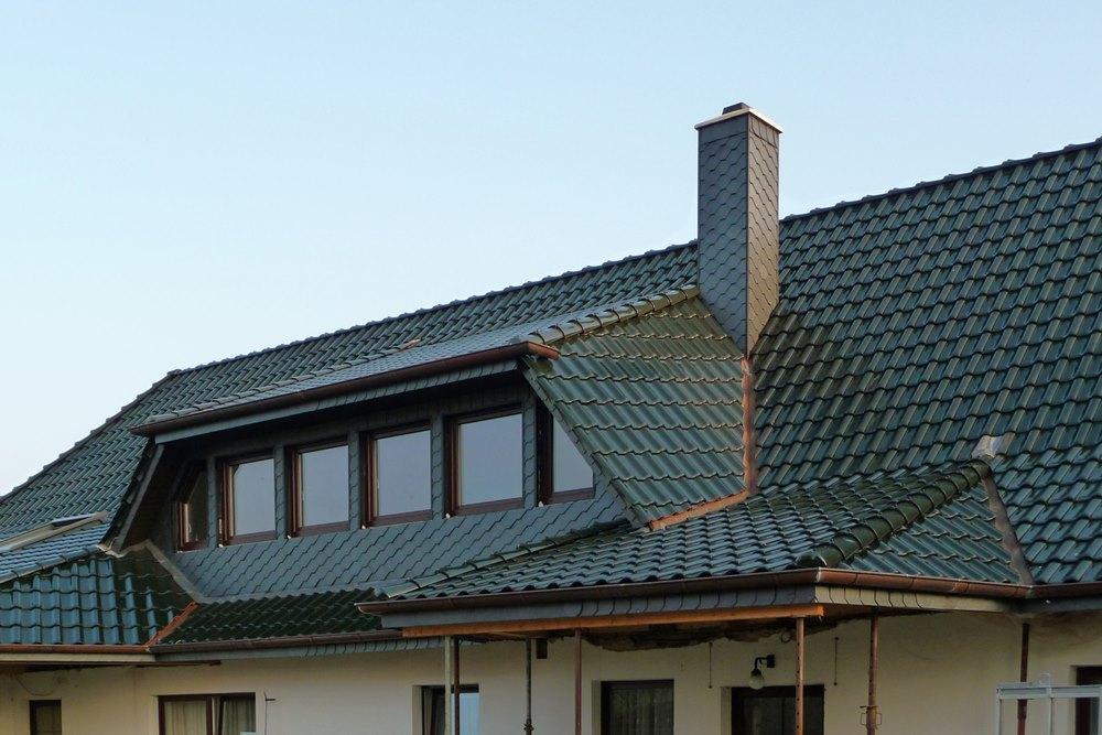 Verschiedene Dachanschlüsse mit Trapezdachgaube und geschiefertem Schornstein